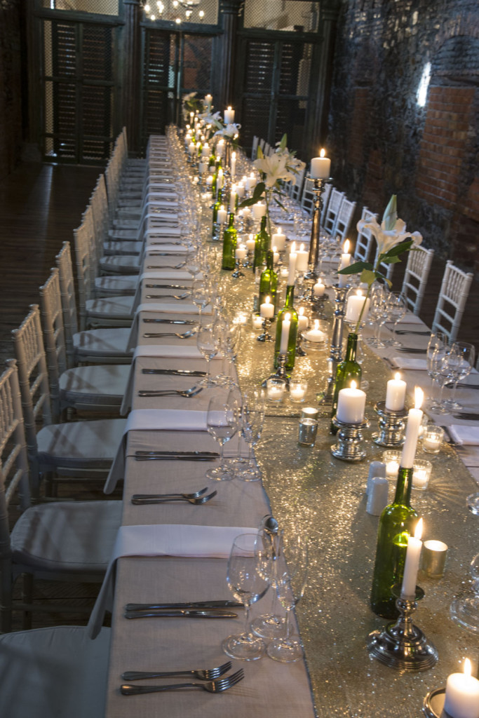 Dinner table in old wine cellar at Nooitgedaght. The shimmering elegance contrasts with rustic cellar walls.